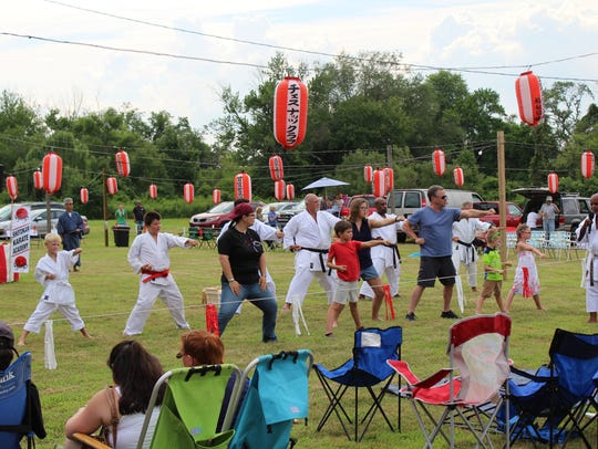 Volunteers participate in a karate demonstration provided