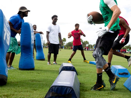 Edgerrin James, center left, watches as participants hustle through a running drill during the 7th Annual Edgerrin James Football Skills Camp at North Park in Ave Maria, Fla. Monday, July 18, 2016. The Immokalee High School product and former NFL all-pro running back hosts the free camp for kids, ages 6-18, to offer help with mechanics, leadership, and teamwork.
