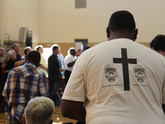 Cornelius White Jr. of Alexandria prays for law enforcement on Thursday. He said he wore his T-shirt in memory of Alexandria Police Department officers David Ezernack and Jay Carruth, who were killed in the line of duty on Feb. 20, 2003.
