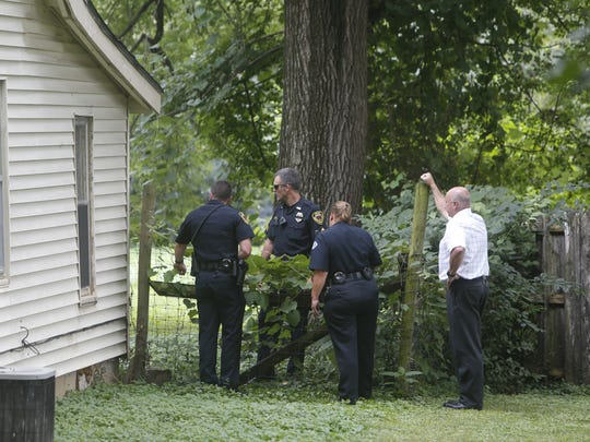 Police look into the backyard in the 2900 block of
