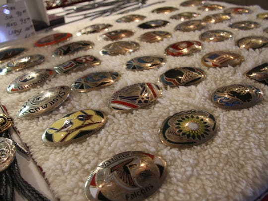 John Johnston designs belt buckles that has professional team logos and people's names.