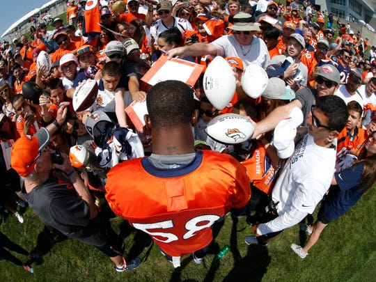 Denver Broncos outside linebacker Von Miller sings autographs for fans after drills during the team's opening session of NFL football training camp Thursday, July 28, 2016 in Englewood, Colo.