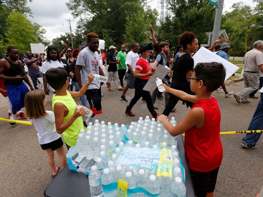 Elijah Luciano, 11, center left, and his twin brother, Isaiah, 11, pass out water to the several hundred protesters as they make their way down North Green Street in Tupelo during a community unity march following the June 18 fatal shooting of Antwun Shumpert by Tupelo Police officer Tyler Cook.