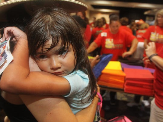 Celimar Silver holds her daughter Nicole, 5, on Sunday at the 17th annual Big Backpack event in downtown Fort Myers. Nicole is starting kindergarten this year.