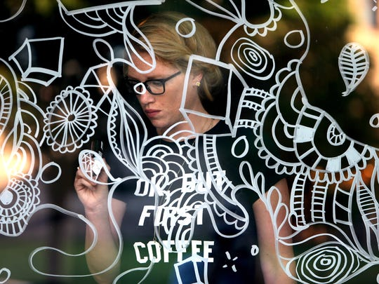 Mendham artist Jen Gunn creates a window display design at SmartWorld Coffee in Morristown. Created with water based Sharpie pens, Gunn uses her intricate designs for local storeowners and her #CreateImaginate illustrations to be fun and interactive for viewers.  July 28, 2016, Morristown, NJ