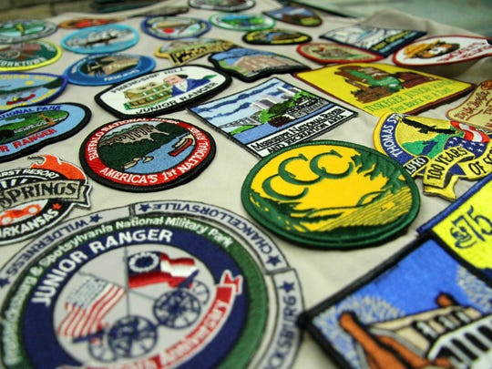 This photo taken July 30, 2016, shows hundreds of Junior Ranger badges from around the country collected by Aida Frey. Since 2010, Aida and her parents have traveled — by car — to 244 national parks and monuments.