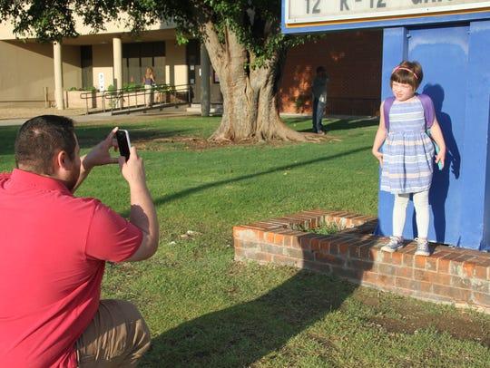 John Kallicoat tries to take a photo of his daughter
