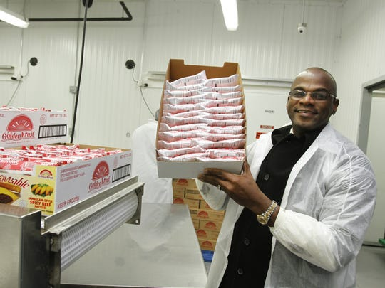 Lowell Hawthorne of Greenburgh, CEO of Golden Krust restaurants, holds a case of meat patties at his Bronx factory in 2013. Golden Krust plans to move its operations to Rockland, to a sprawling $37 million bakery, distribution center and corporate facility it will build on Route 303 in Orangetown, according to documents filed with the Rockland Industrial Development Agency.