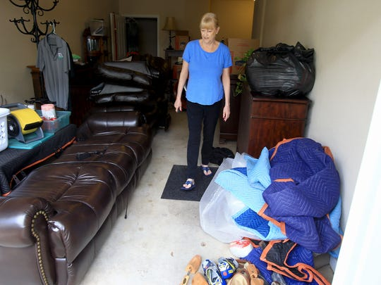 Debbie Geraci walks in her garage were she placed furniture after water flooded her apartment at the Highlands of Grand Pointe apartments in Lafayette.