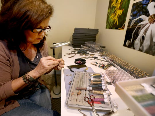 Sandra Arnold shows how she sews tiny seed beads together
