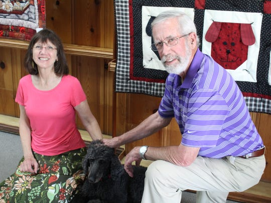 Sylvia Dorney, left, and Bill Dorney, right, with their dog Lovey. The two say the blue black poodle might miss the business the most, between the three of them.