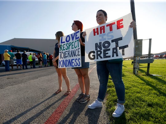 Kristina Libbey, from left, Habley Anderson and Heather Bird, of Austin, hold signs as people enter a campaign rally where Republican presidential candidate Donald Trump was to speak Tuesday near Austin.