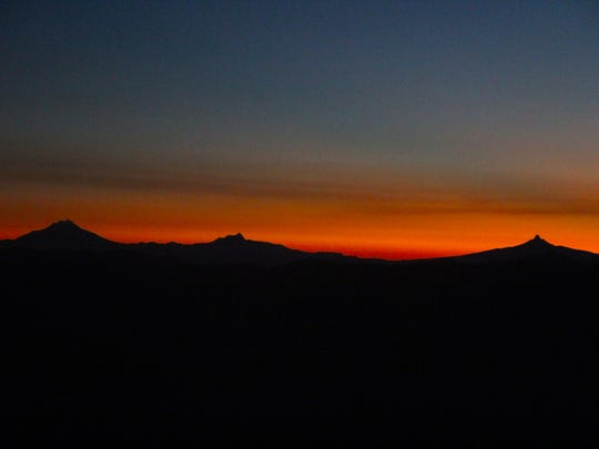 The sun rises over Mount Jefferson, Three Fingered Jack and Mount Washington.