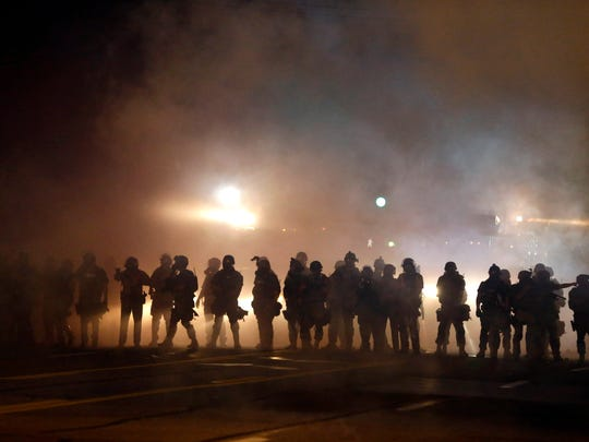 Police walk through a cloud of smoke and tear gas during