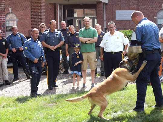 Juliet Nigara of Mountain Lakes looks on for a Sheriff's K9 demonstration with her father Anthony and Morris County Sheriff's Officers as the 6-year-old was honored at the Morris County courthouse by the Sheriff's Office as their 'Hero for a Day.' August 26, 2016, Morristown, NJ