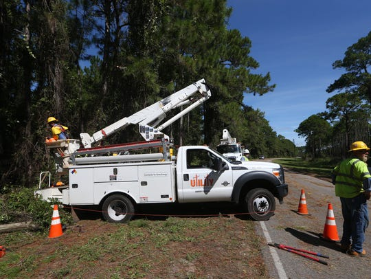 Utility workers repair power lines along the highway