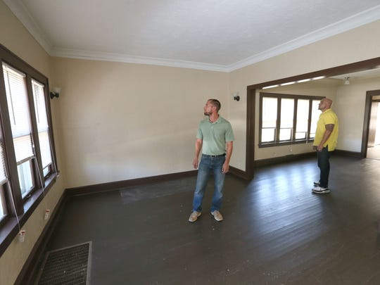 Rob Goral (left) and Paul Poniewaz, both of Real Property Management, look over the rehab job done on the living room of the duplex on W. Center St.