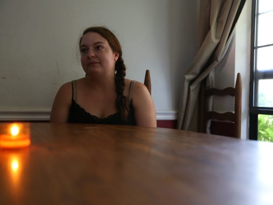 Alexis Bell sits in her dining room with a candle lit