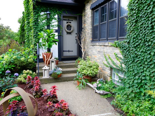 The porch of florist Deb Fowler's Wauwatosa home is decorated in a botanical fall theme, featuring a variety of plants and shrubs.