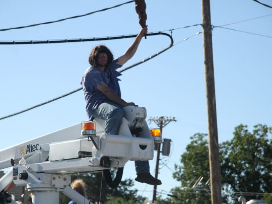 Carlsbad High School Caveman sits on the top a cherry picker on a truck.