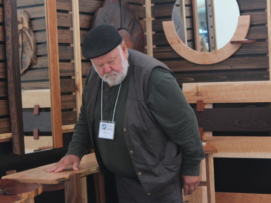 Patrick Plautz adjusts one of his wooden furniture pieces at Wausau's Artrageous on Saturday. Plautz sells reclaimed wood furniture at his shop called Patrick J's Imagination.