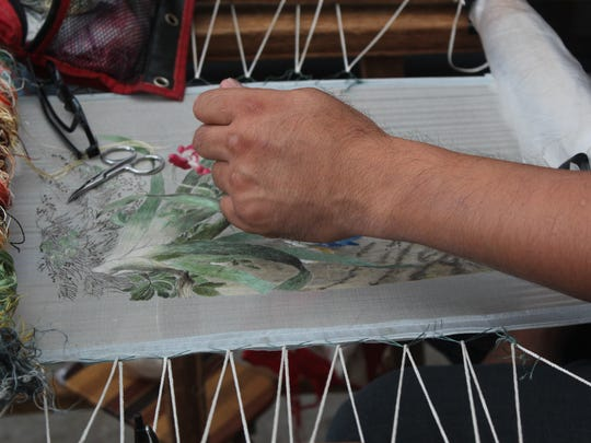 Vern Yan hand stitches silk to create art at Wausau's Artrageous on Saturday.