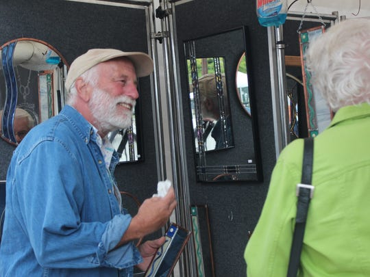 Warren Slocum talks to a customer at Artrageous about his stained glass mirrors. Slocum works in St. Croix county.