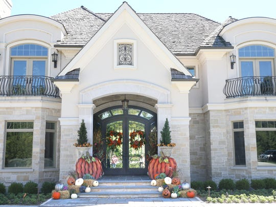 Ann Schneider used large items, like metal pumpkins and large wreaths, to add fall drama to a stately front porch.