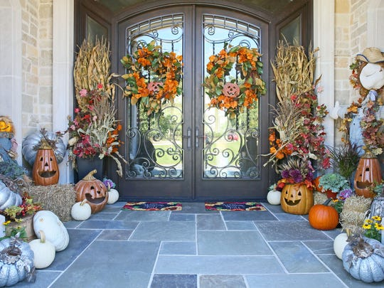 Heirloom pumpkins, jack-o-lanterns and fall foliage line the entry of a front porch that Ann Schneider decorated for fall.