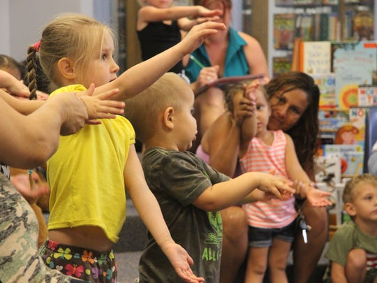 Kids at Tuesday's preschool story time danced to a song about sharks. They mimicked a father and mother shark as well as a baby shark and rowing a boat.