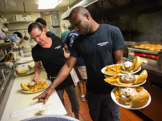 Jessica Pegurri, left, and Dennis Samuels double check their orders in the kitchen at Brooks Gourmet Burgers & Dogs in Naples, Florida on Friday, Sept. 16, 2016. National Cheeseburger Day is September 18th. Brooks made TripAdvisor's America's 10 Most Delectable Burger Joints List for two consecutive years in 2015 & 2016.
