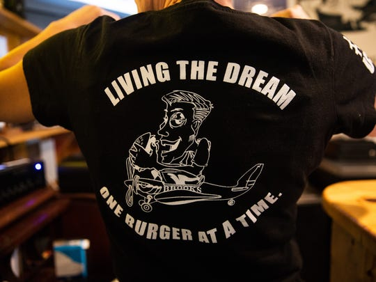 The graphic on the back of the staff shirts at Brooks Gourmet Burgers & Dogs, which was originally a customer napkin drawing, shows owner, Todd Brooks, eating a burger. National Cheeseburger Day is September 18th. Brooks made TripAdvisor's America's 10 Most Delectable Burger Joints List for two consecutive years in 2015 & 2016.
