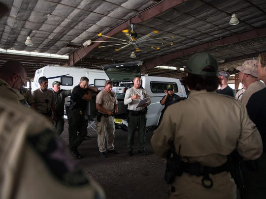 Sgt. Dale Dear leads an end of day meeting at the Collier County Fairgrounds in Orangetree, Florida on Saturday, Sept. 17, 2016. The Collier County Sheriff's Office is searching for a missing man that disappeared into the woods in Orangetree late last night. Although the effort was scaled down due to weather this evening, the team is still in a rescue effort, resuming the search tomorrow morning with rescue dogs and a dive team.