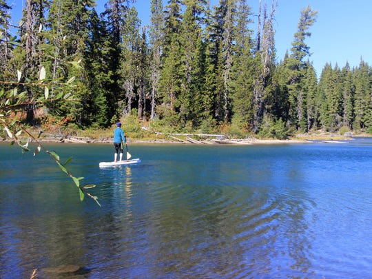 A stand up paddleboard peruses Waldo Lake.