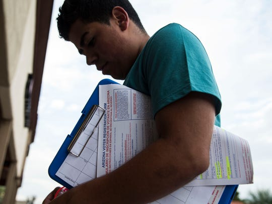 Fred Oaxaca, 21, asks people to register to vote in a Fry's parking lot in Phoenix.