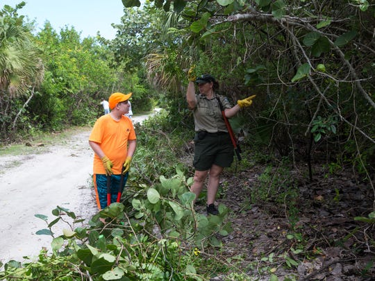Park Ranger Katie Moses, right, points out a poison ivy bush to Lucian Brown, 12, of Ft. Myers during the Public Lands Workday at Lovers Key State Park in Bonita Springs, Florida on Saturday, Sept. 24, 2016. Lovers Key State Park Rangers and volunteers helped maintain the trails as a part of National Public Lands Day, a nationwide event established by the National Environmental Educational Foundation (NEEF) to celebrate the public lands that make up 30% of the United States.