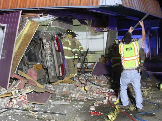 Williamston firefighter Phillip Ellison shores up a building as other firefighters cut two people from the wreckage of a car. The car crashed into a building at the car wash on East Main Street at Greenville Drive.