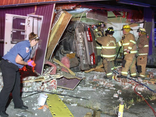 Williamston firefighters and Medshore Ambulance Service personnel work at the scene of a car wreck early Wednesday morning. A car crashed into a building.