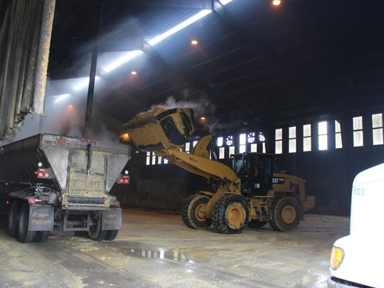 A payloader fills a farm semi with a steaming load
