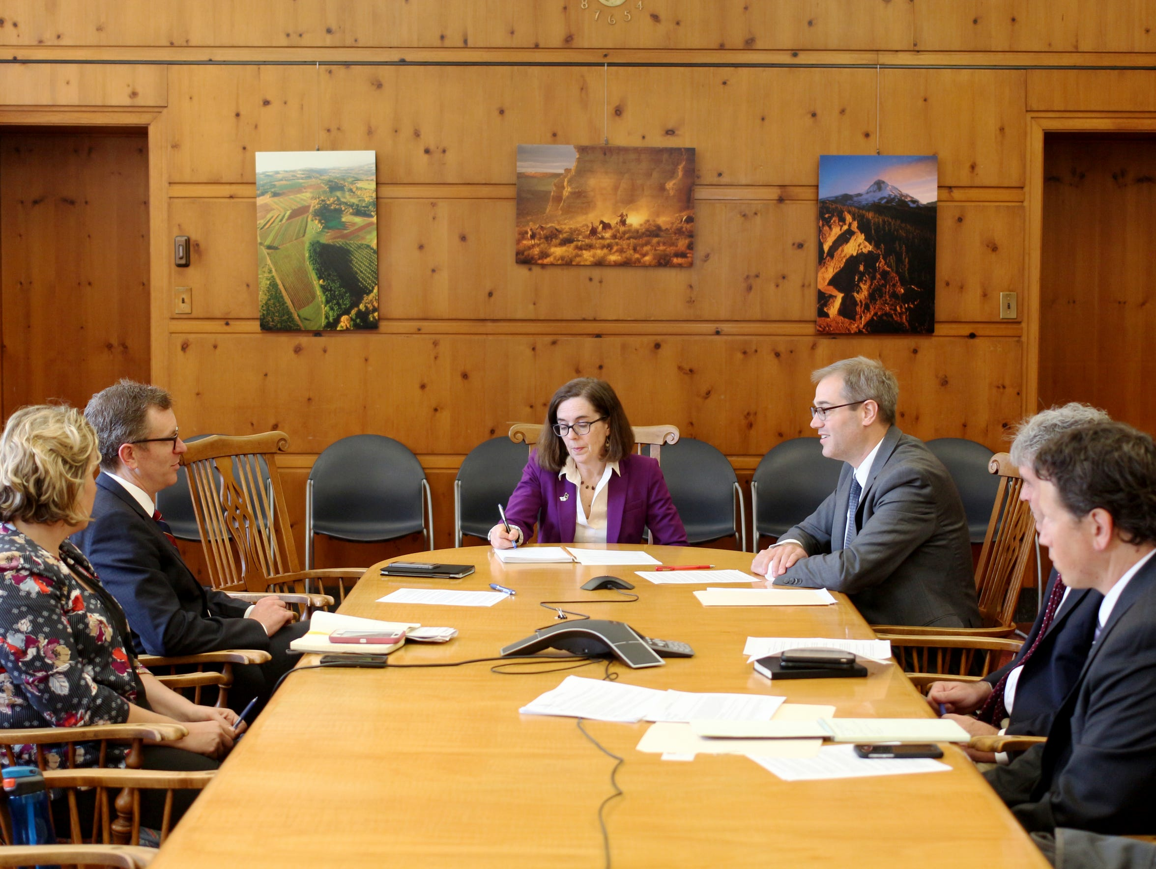 Oregon Gov. Kate Brown, center, being briefed by economic