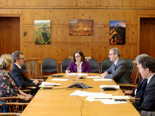Oregon Gov. Kate Brown, center, being briefed by economic advisers in her conference room at the Capitol Building on Sept. 21, 2016.