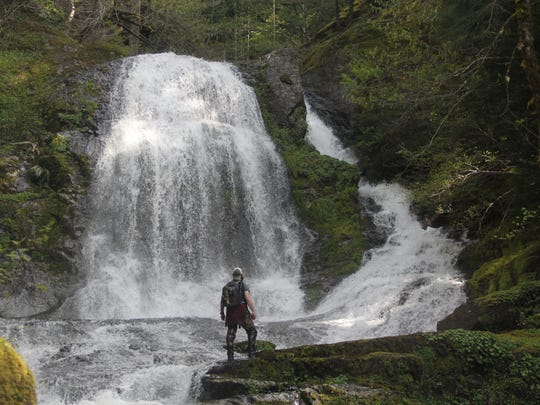 Jeff Green stands in the spray of Dan Falls in the Family Falls system of waterfalls on upper Henline Creek.