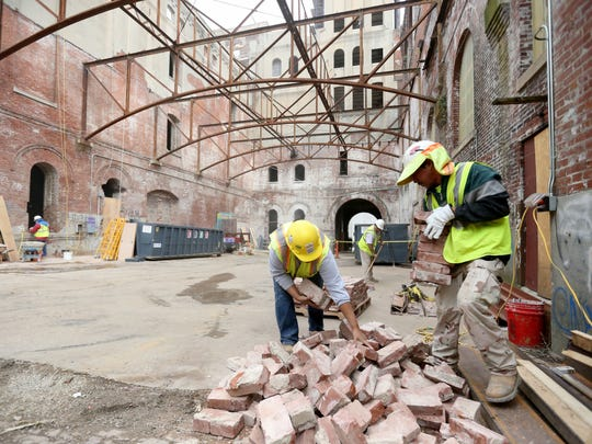 Icsa Manzanares and Jesus Corneji sort bricks as demolition work continues to turn the historic Tennessee Brewery building into apartments.