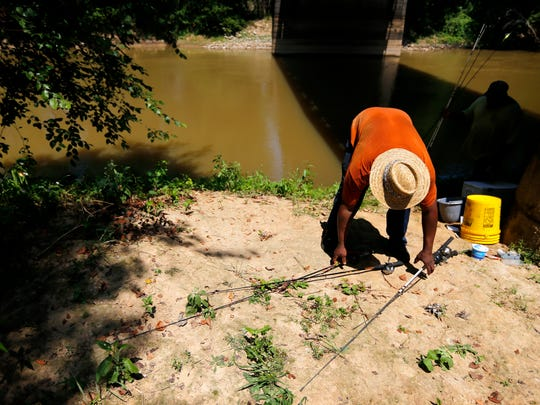 Jermain Jarrett gathers his rods after calling it a day while fishing with friend Dwayne Rivers under the Tennessee 76 bridge that passes over the Hatchie River outside Brownsville, Tenn.