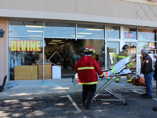 A woman was trapped under a BMW that drove through a dry cleaners Friday.