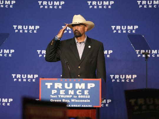 Milwaukee County Sheriff David Clarke Jr. salutes the crowd and the flag as he takes the podium to warm up the crowd for Donald Trump.