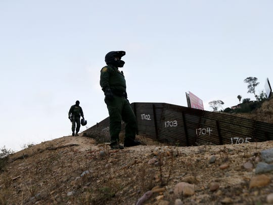 In this Wednesday, June 22, 2016, file photo, Border Patrol agents look over the primary fence separating Tijuana, Mexico, right, and San Diego in San Diego. An estimated 40 percent of the 11.4 million people in the U.S. illegally overstayed visas, a crucial but often overlooked fact in the immigration debate. More people overstayed visas than were caught crossing the border illegally.