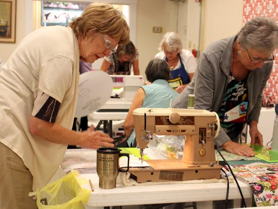 Val Irish, left, and Janet St.Cyr work on their quilts