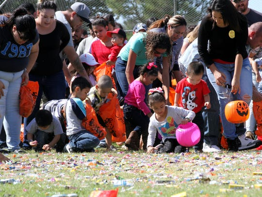 Children and adults scramble for the pieces of candy