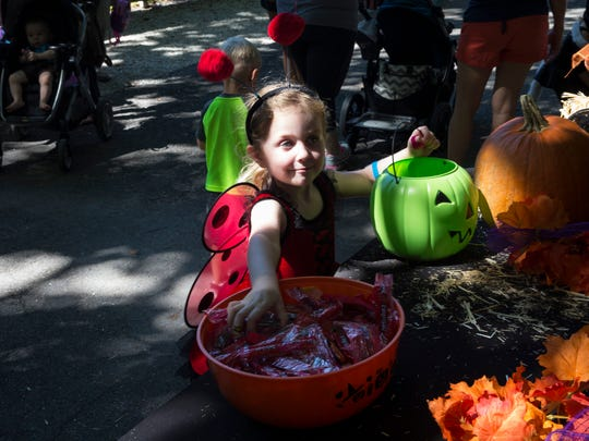 Palmer McClanahan, 4, smiles as she grabs some candy while trick or treating during the Boo at the Zoo event at Naples Zoo on Friday, Oct. 21, 2016. For 3 days, children in costume will receive free admission and get to enjoy a trick or treat trail, costume contests and games at Boo Town.